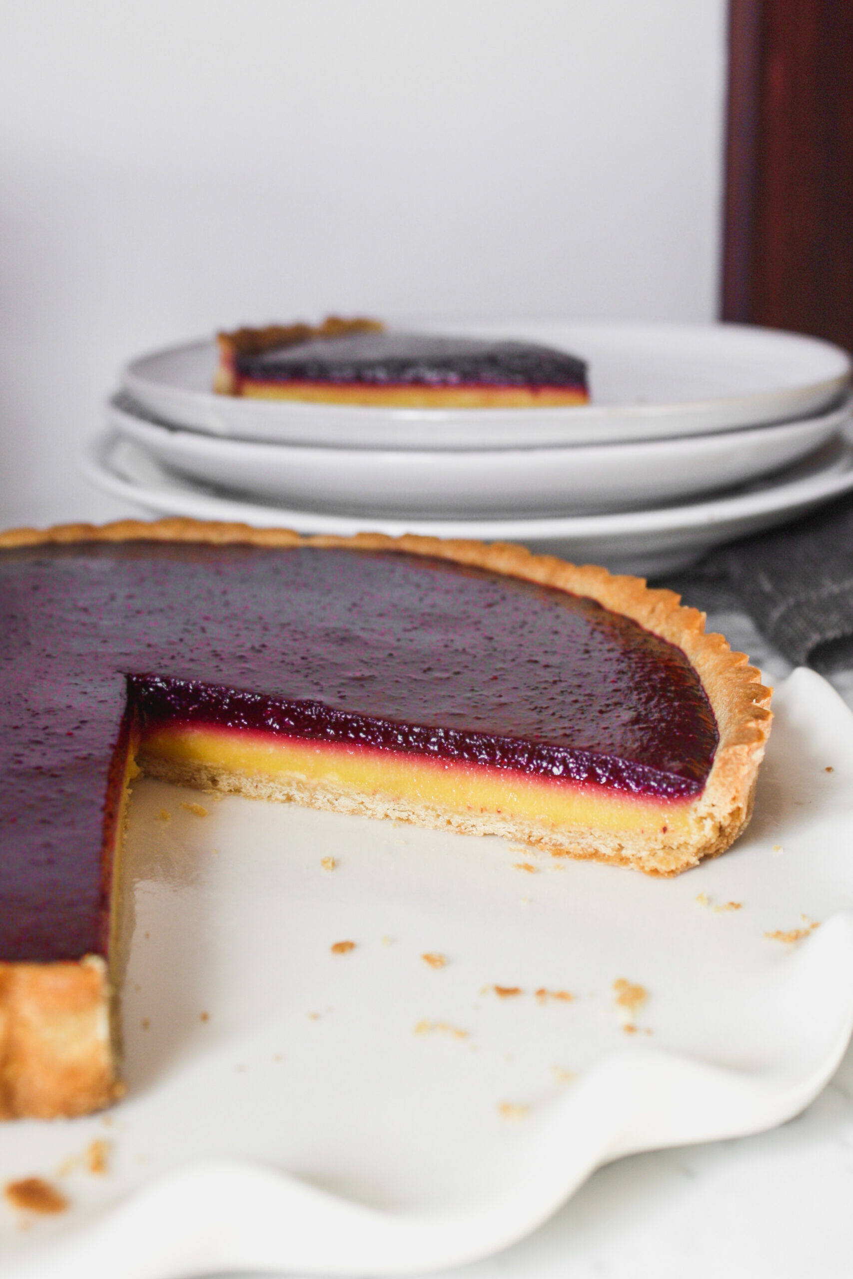 Tart with yellow and purple layers, set on top of a white plate on a marble surface.