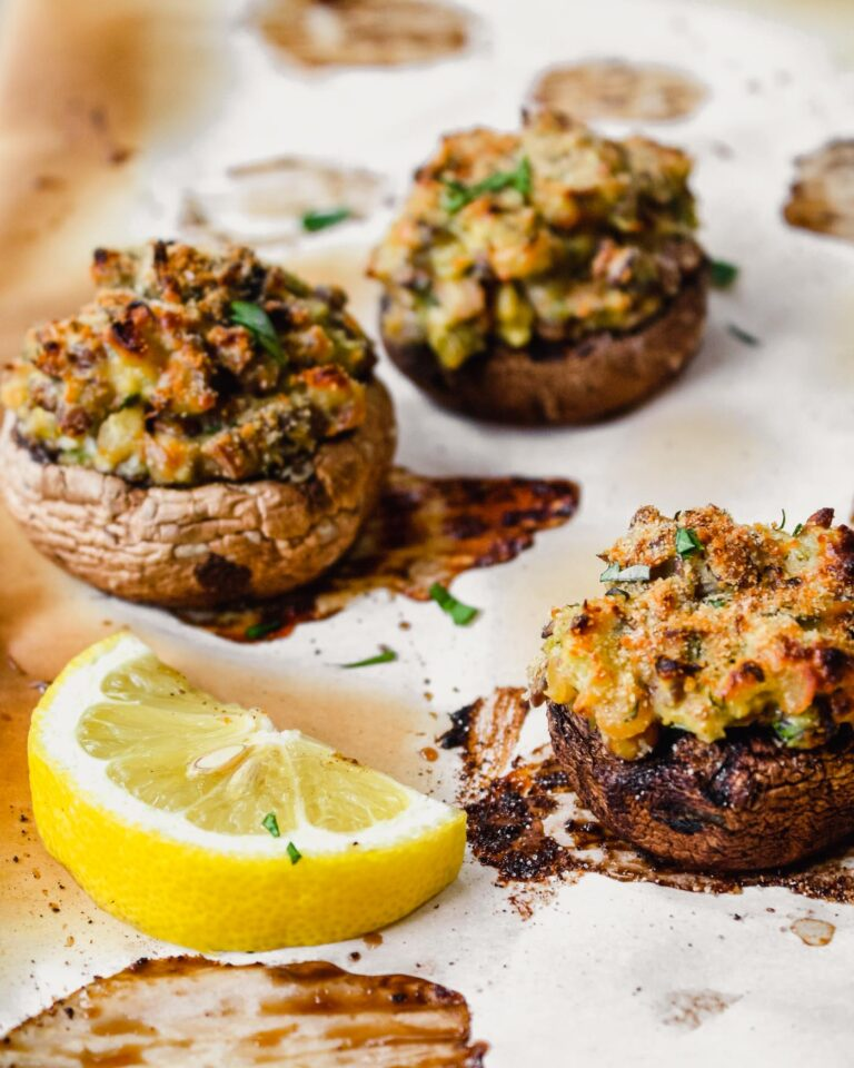 Stuffed cremini mushrooms on a baked piece of parchment paper with a lemon wedge in the center