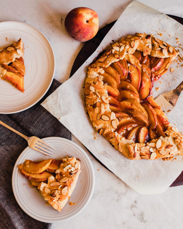 photo of a peach galette on a piece of parchment paper with slices on plates scattered around.