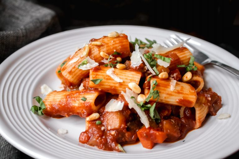 Photograph of rigatoni pasta tossed with bolognese sauce on a white plate with black background