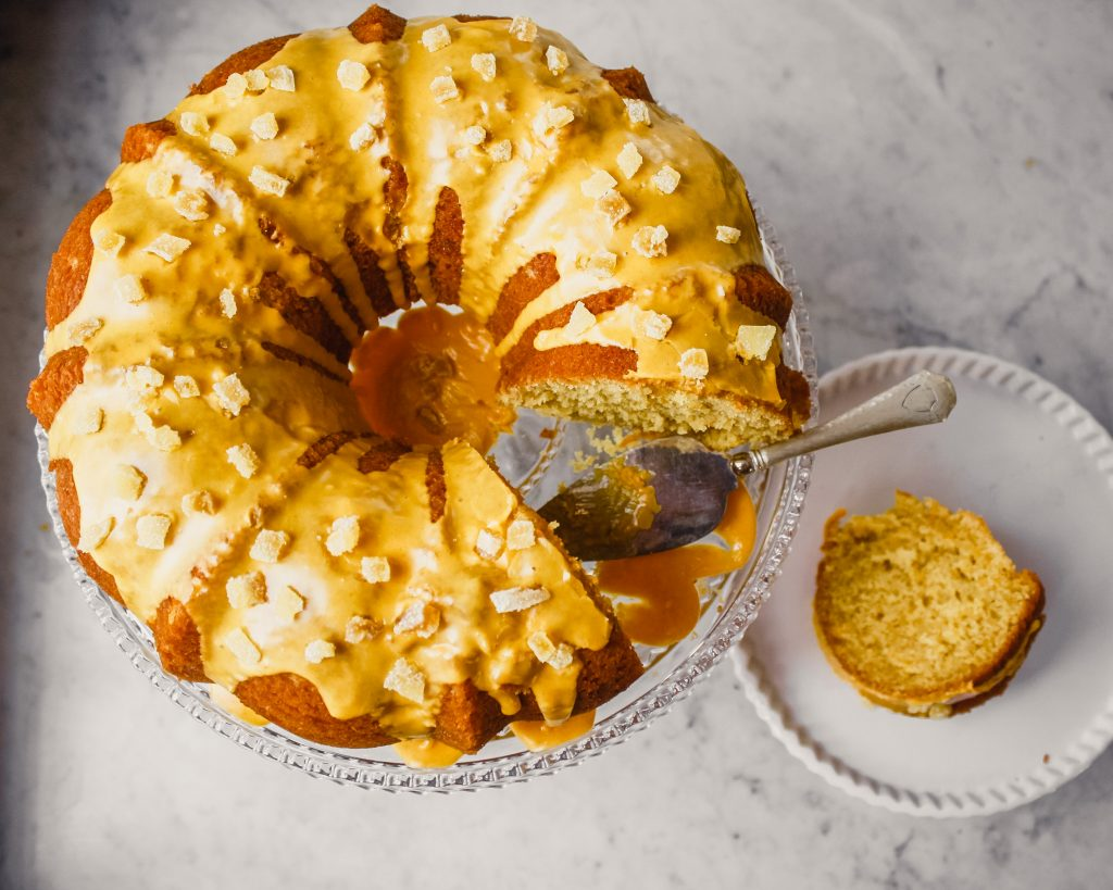 Photograph of orange and ginger bundt cake with turmeric glaze on glass cake stand