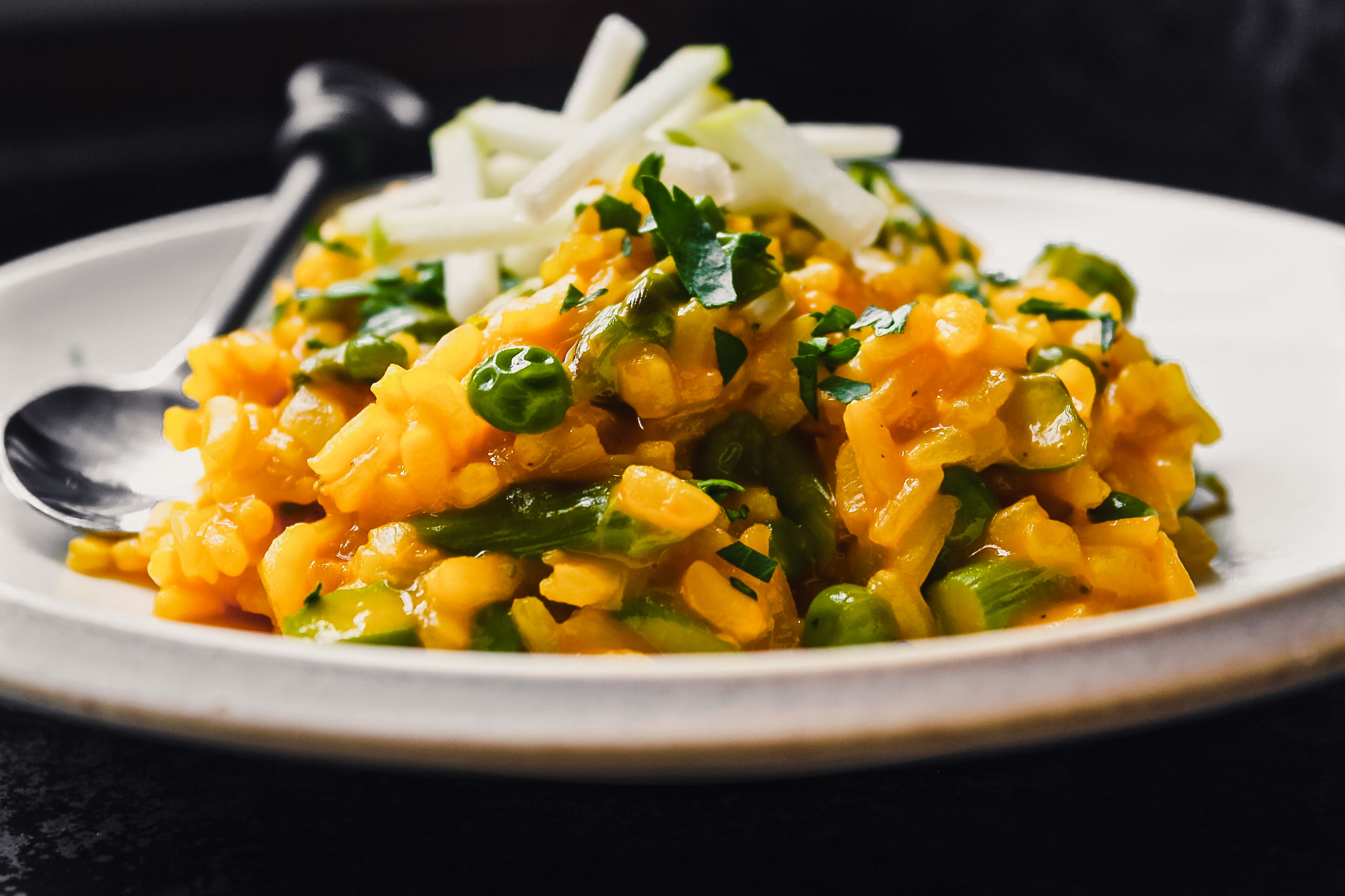 Close up photo of carrot risotto with peas and asparagus
