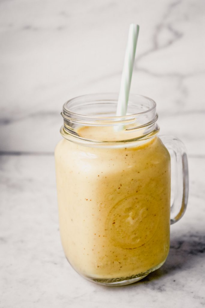 Side angle of a glass ball jar filled with a yellow-range smoothie set on a white marble table.