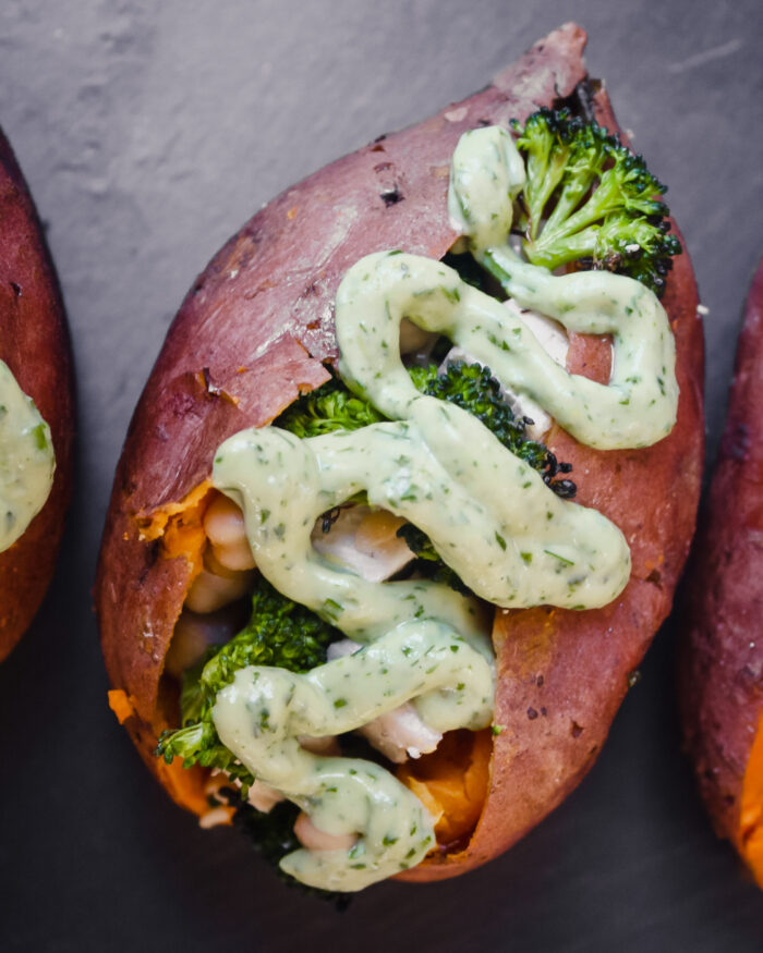 Overhead photograph of stuffed sweet potatoes drizzled with a green goddess dressing