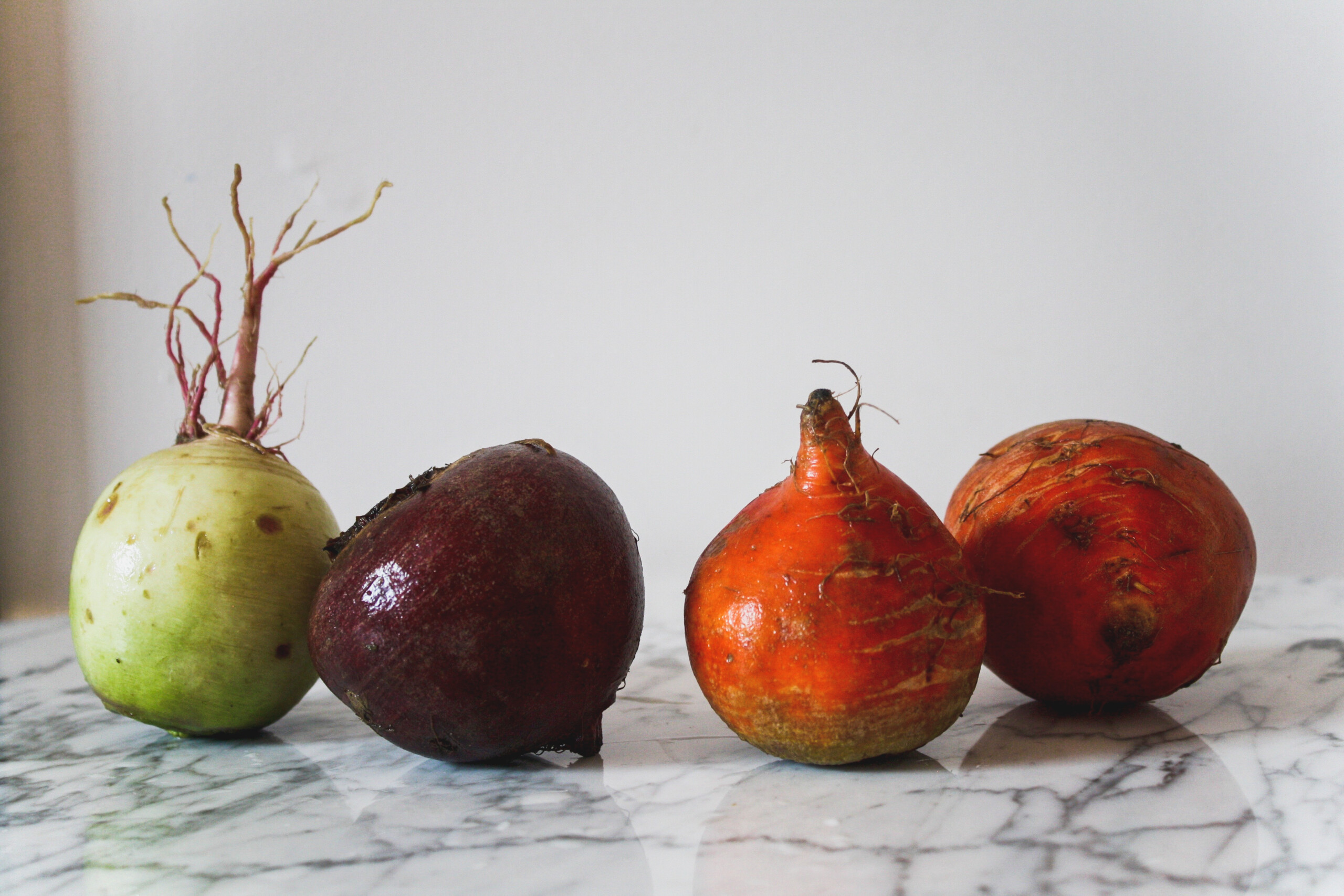Photograph of beets set on a white marble table