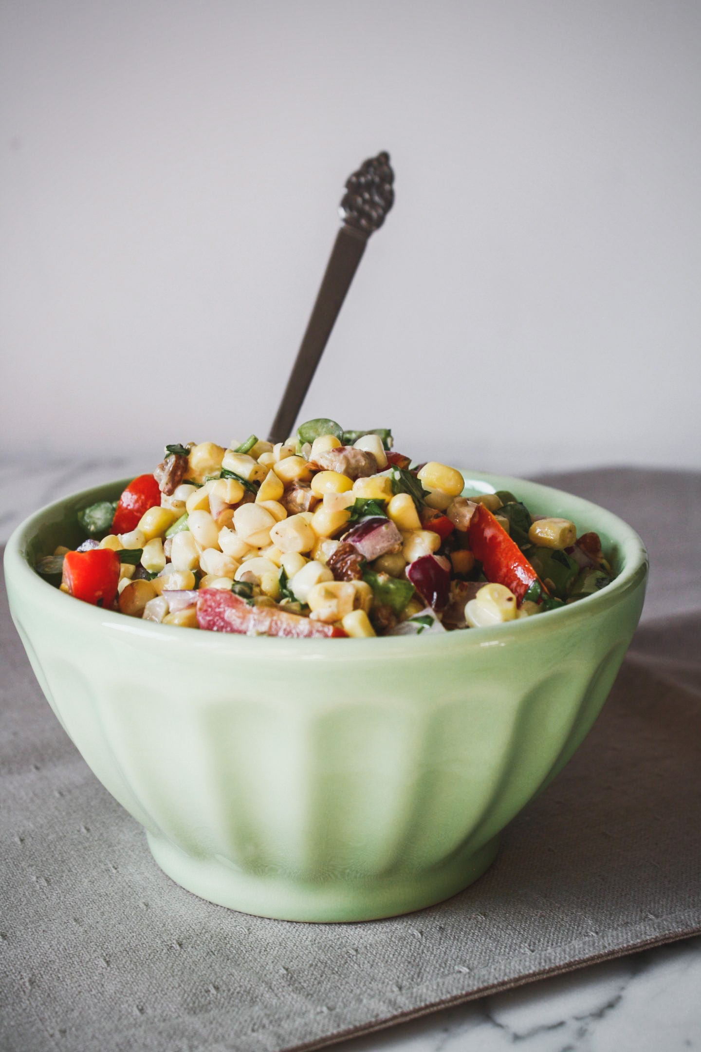 Photograph of corn salad in a green bowl set on a marble table.