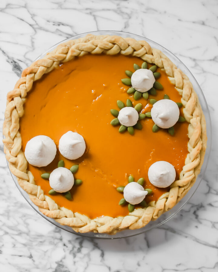 Photography of a pumpkin pie garnished with spiced meringue cookies and pepitas.