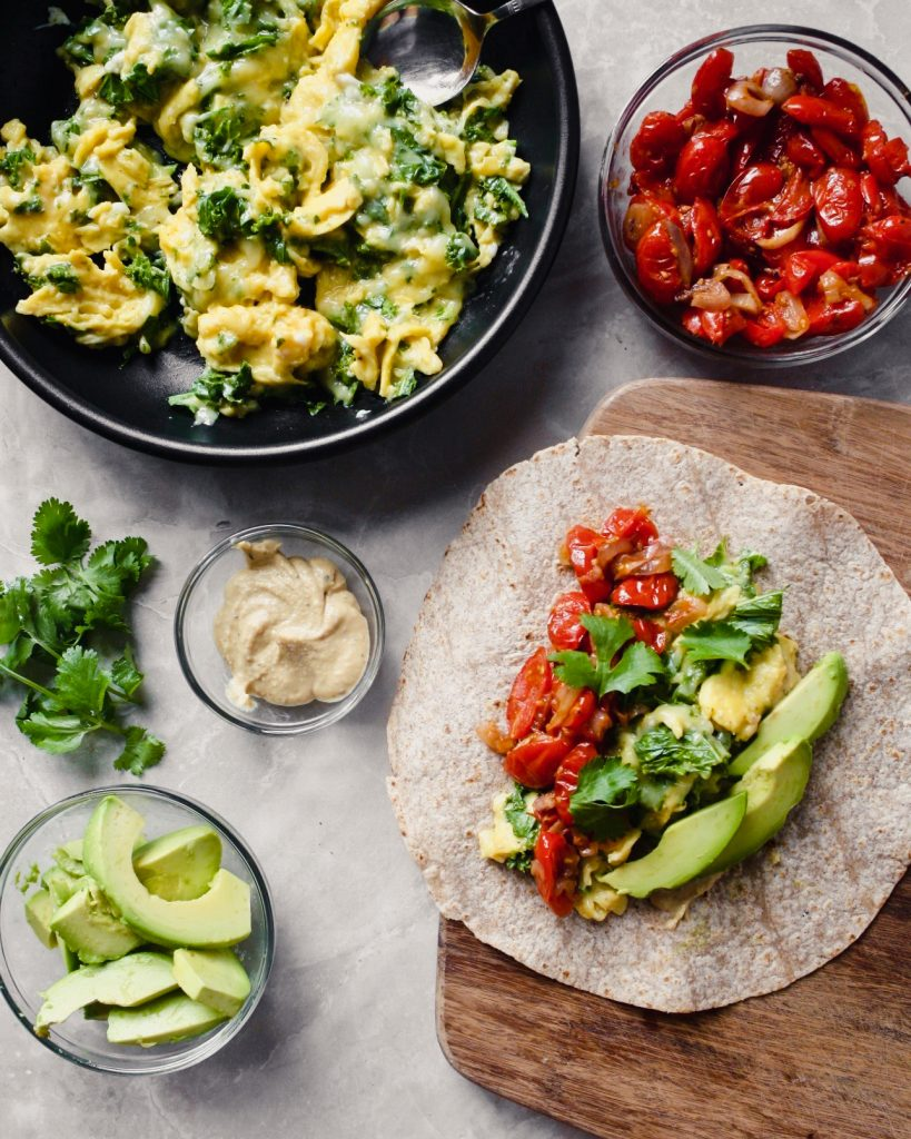 overhead photograph of preparation of vegetarian breakfast burritos on a butting board.