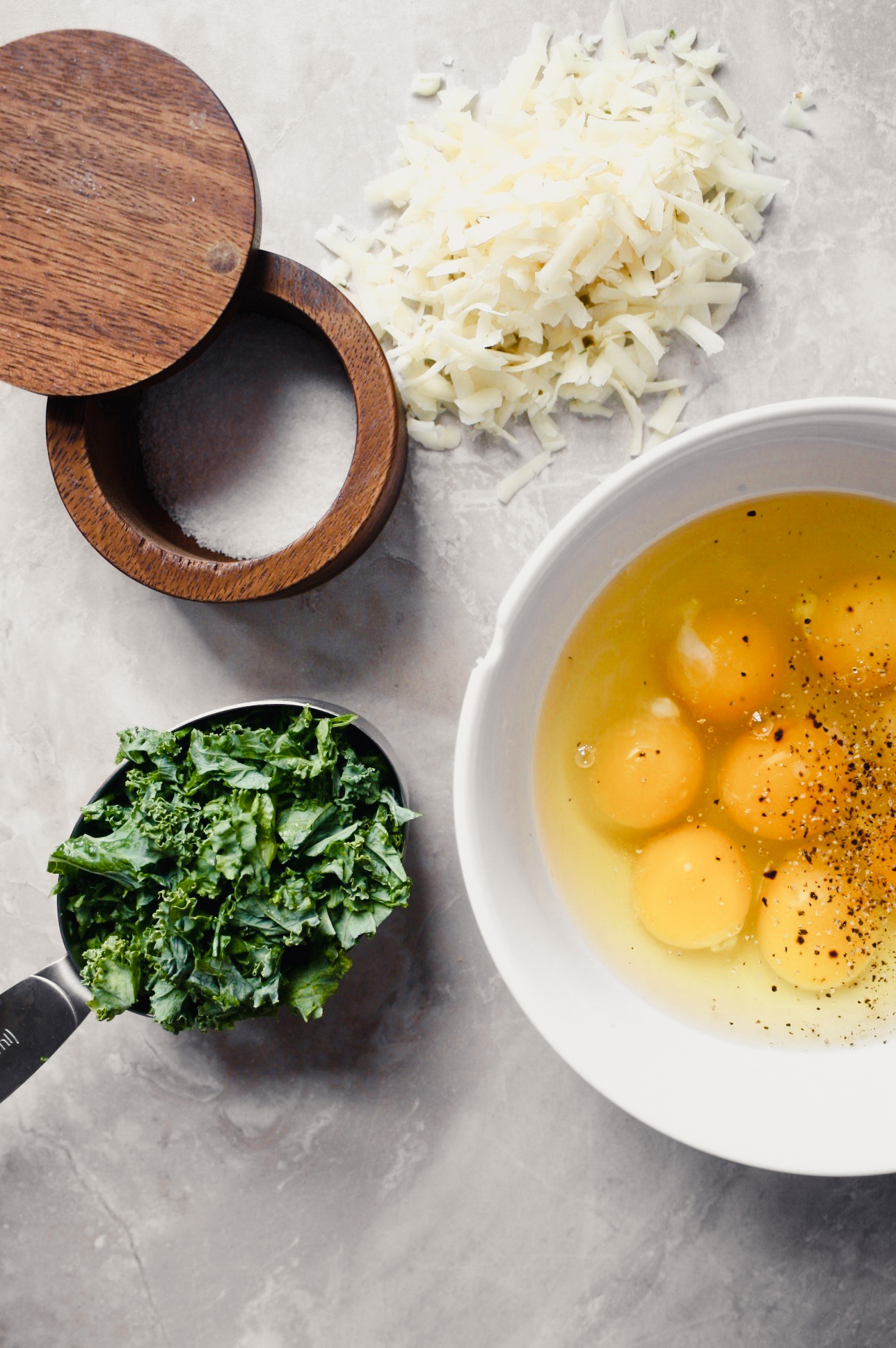 Overhead photograph of a bowl of eggs, shredded cheese and fresh kale