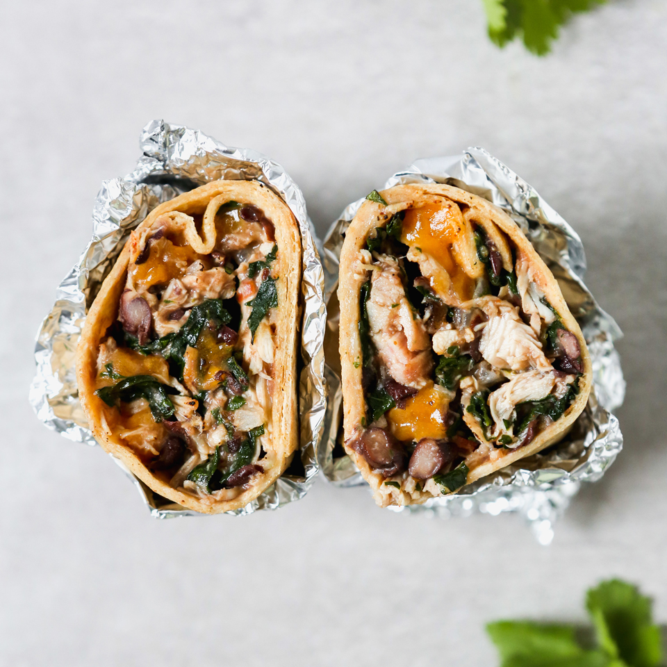 Photograph of chicken burrito cut in half.