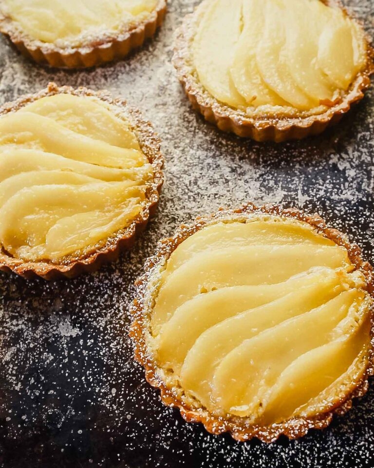 Overhead image of a mini tarts on a balking sheet topped with layered of poaches pears