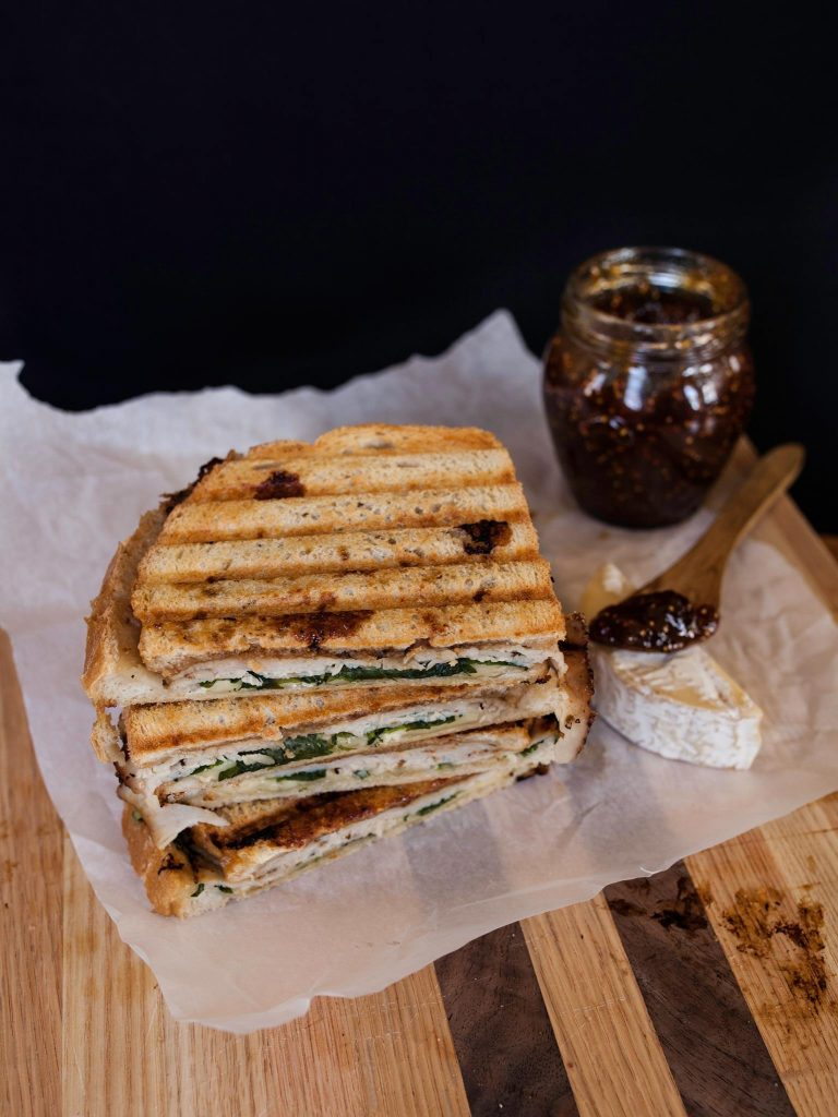 Turkey and Fig Panini set on parchment paper on a cutting board | Zestful Kitchen