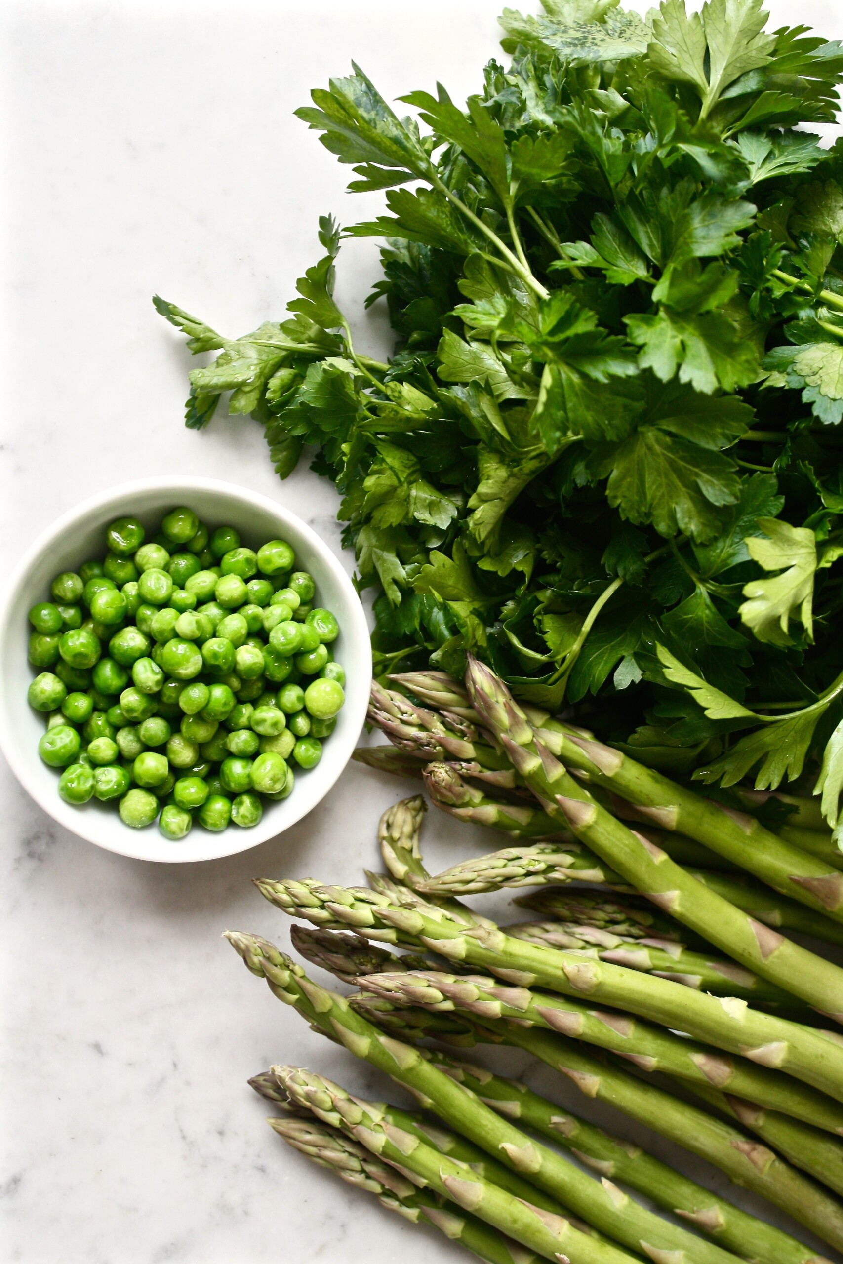 Photograph of asparagus, parsley and peas scattered on a marble table