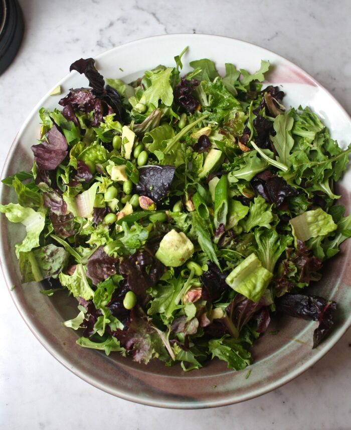 Large green salad in a bowl set on a marble table