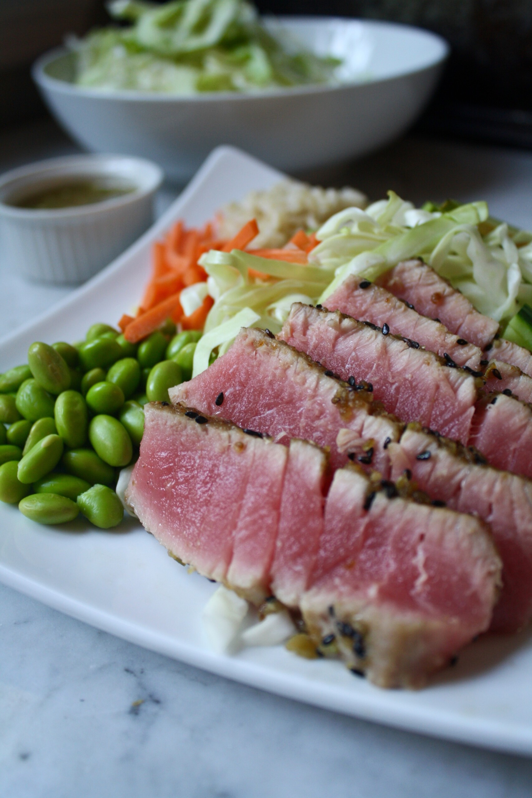 Photograph of Wasabi Crusted Ahi Tuna on a plate with edamame, cabbage, and carrots.
