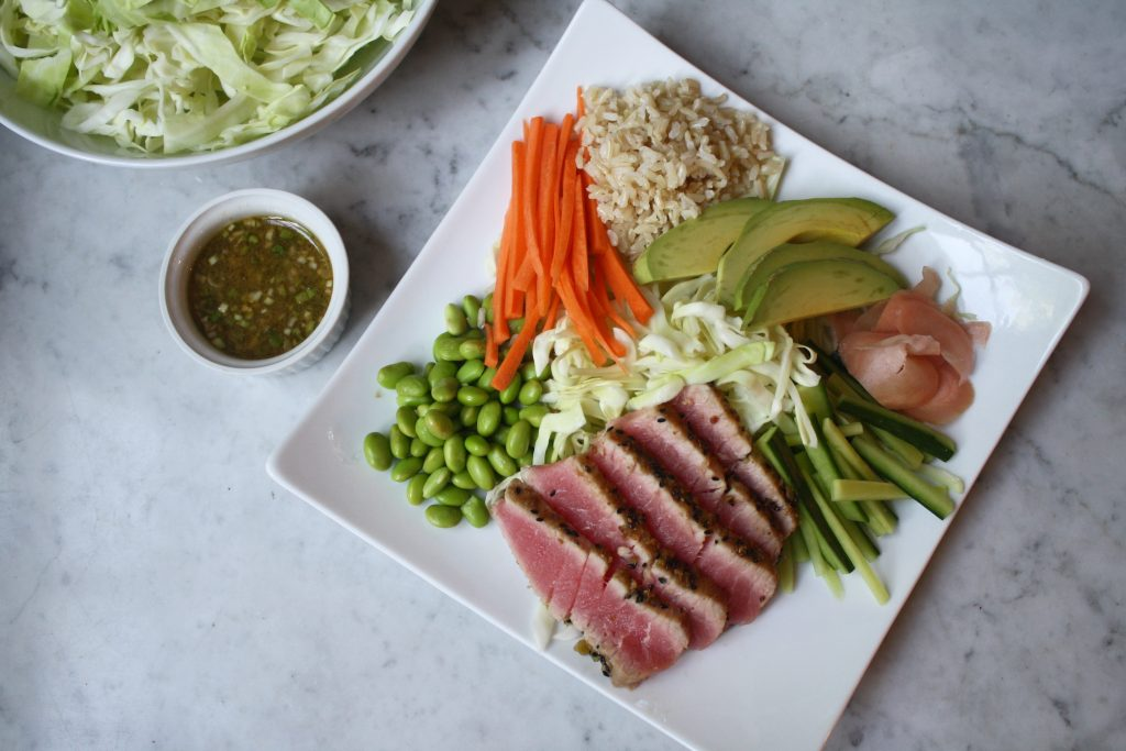 Photograph wasabi crusted tuna set on a white place with brown rice, carrots, cabbage, cucumbers and pickled ginger.