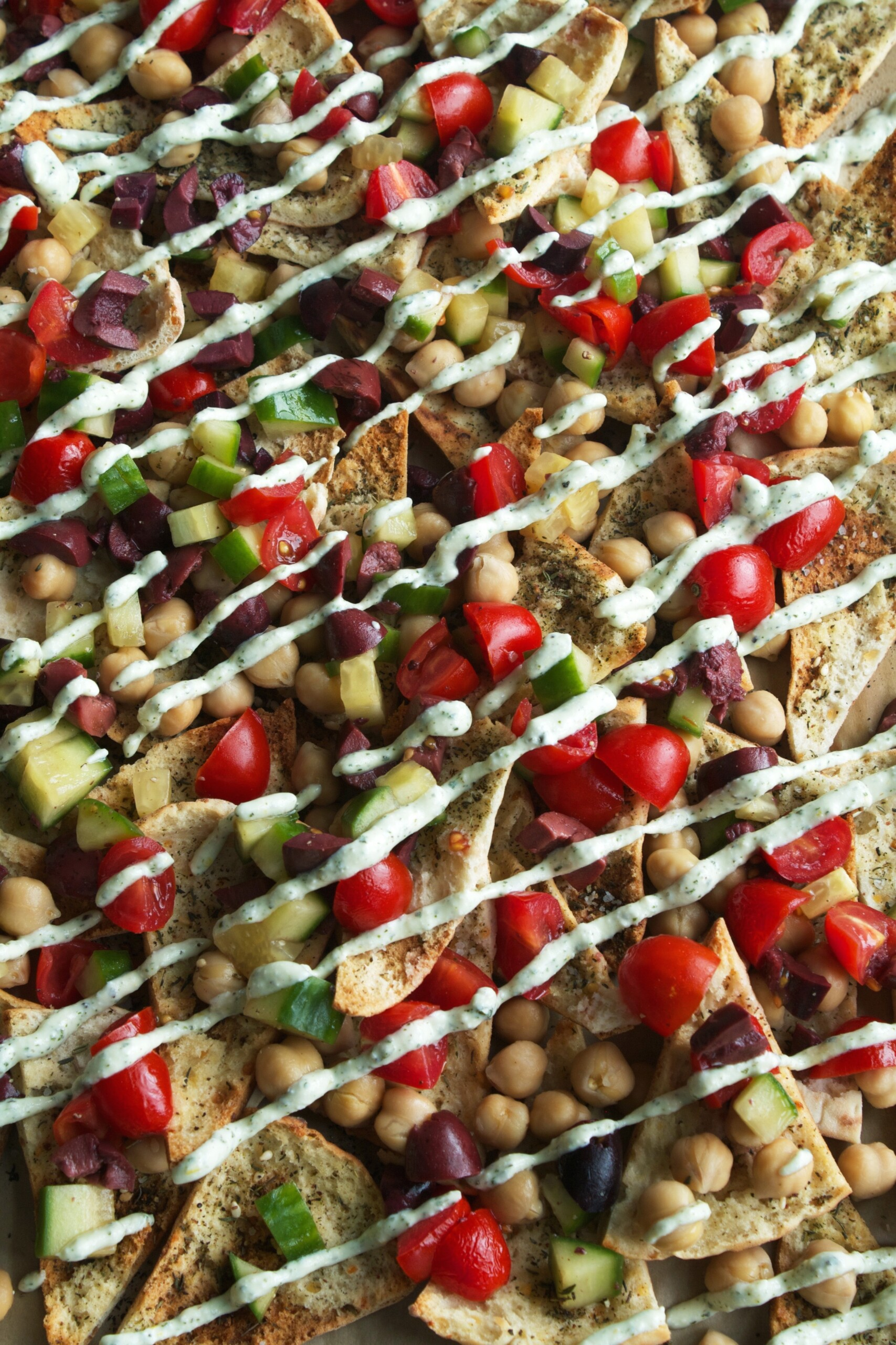 pita chips layered on a baking sheet topped with tomatoes, cucumbers, olives, chickpeas and a drizzle of yogurt-feta sauce