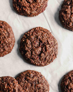 Photograph of chocolate cookies arranged on a piece of parchment paper