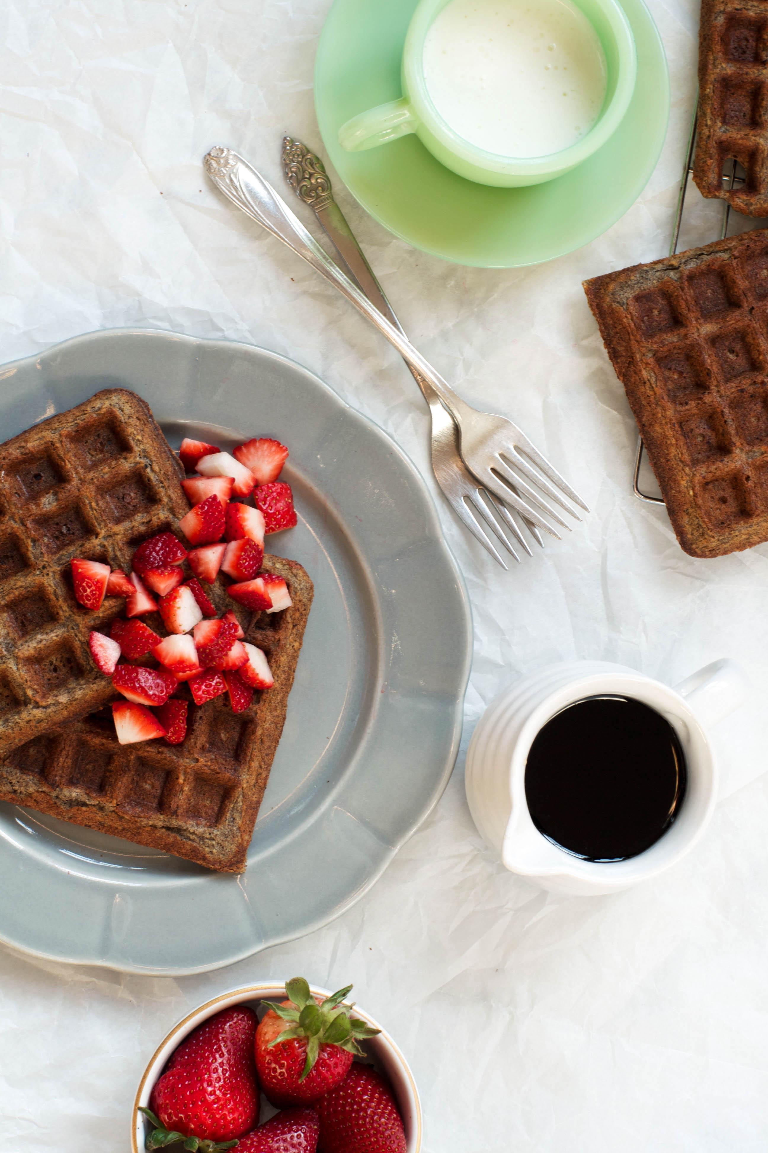 Gluten Free Buckwheat Waffles set on a gray plate with strawberries | Zestful Kitchen