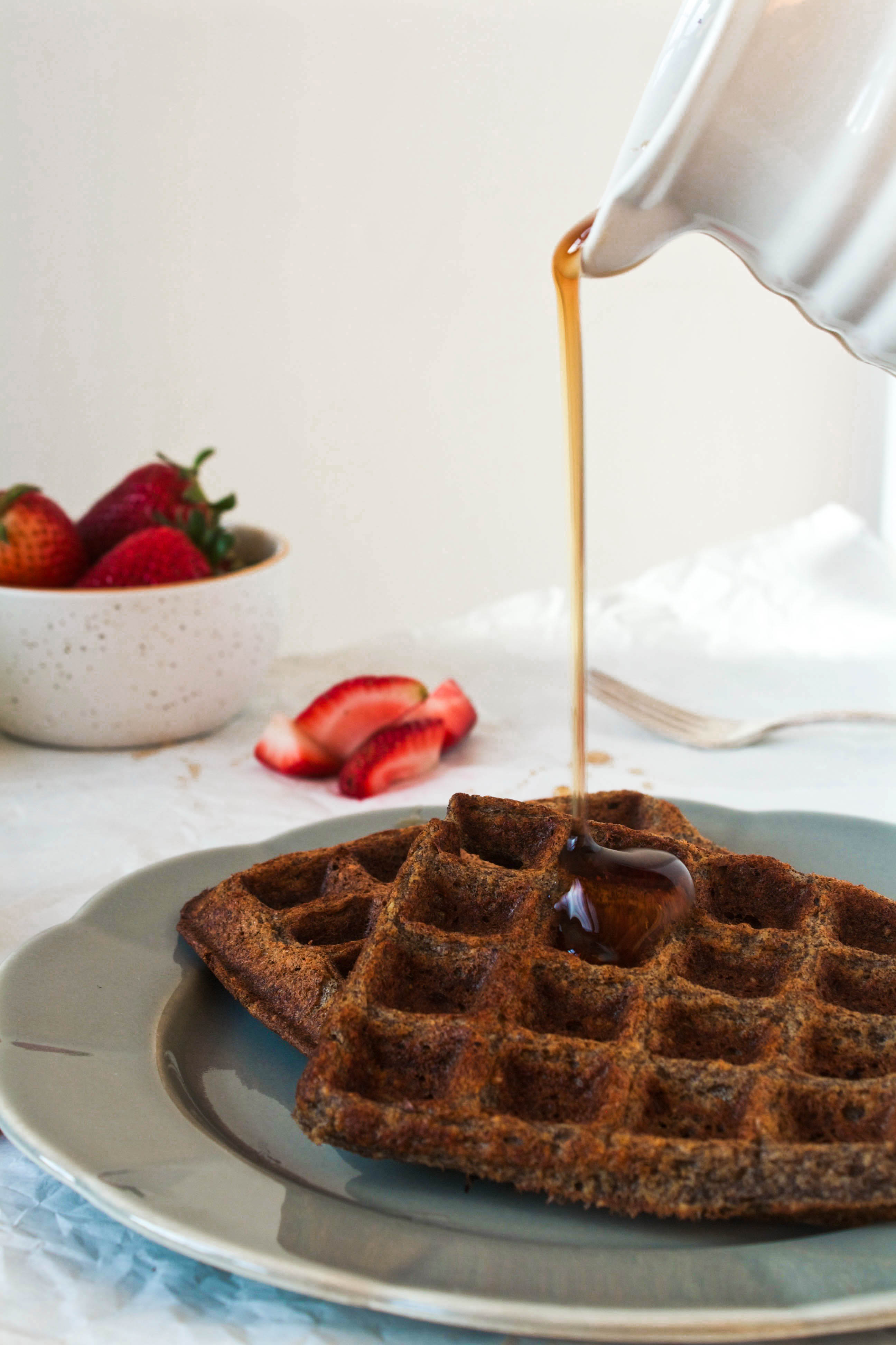 Gluten Free Buckwheat Waffles on a gray plate with a stream of syrup pouring over them | Zestful Kitchen
