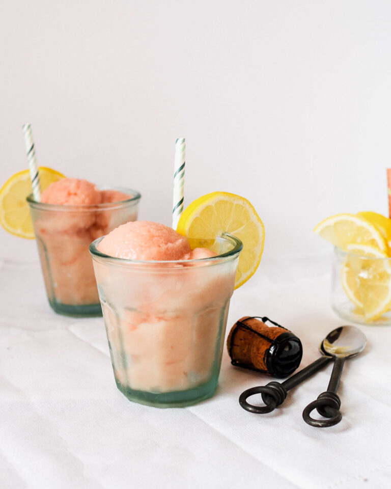 Scoops of rhubarb ice in glasses with lemon slices and spoons.