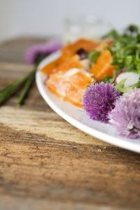 Close up of purple chive blossoms and smoked trout on a white plate
