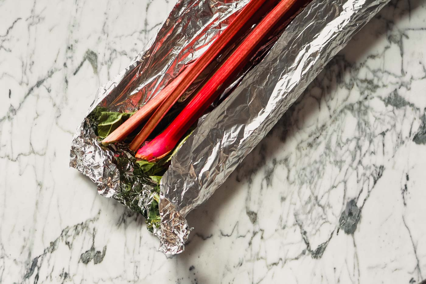 Photograph of stalks of rhubarb partially wrapped in foil