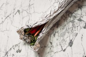 Photograph of stalks of rhubarb mostly wrapped in foil