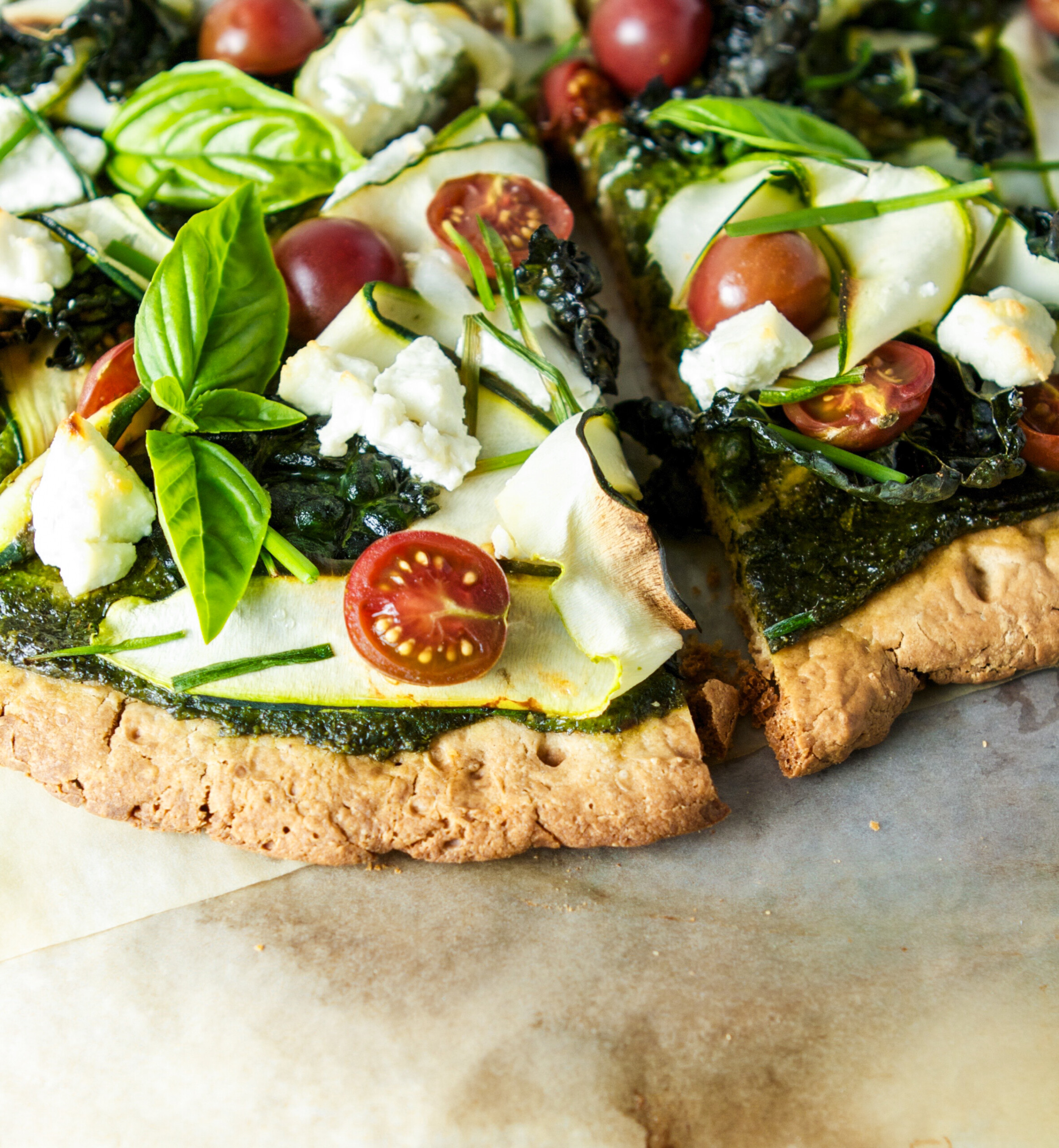 Photograph of pizza topped with pesto, cheese, tomatoes and basil, set on white paper