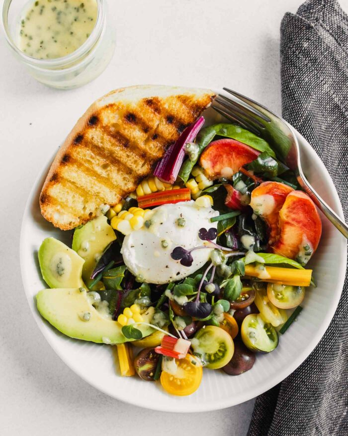 white bowl filled with veggies and fruit, topped with a poached egg and toasted bread