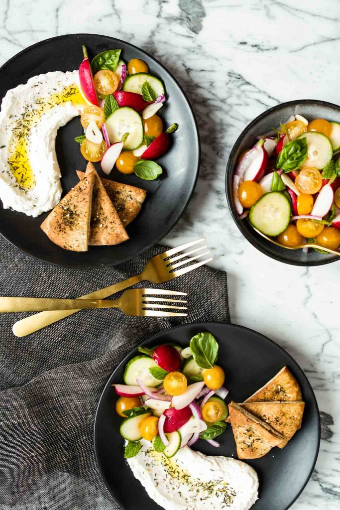 image of vegetables and labneh on a black plate with pita wedges