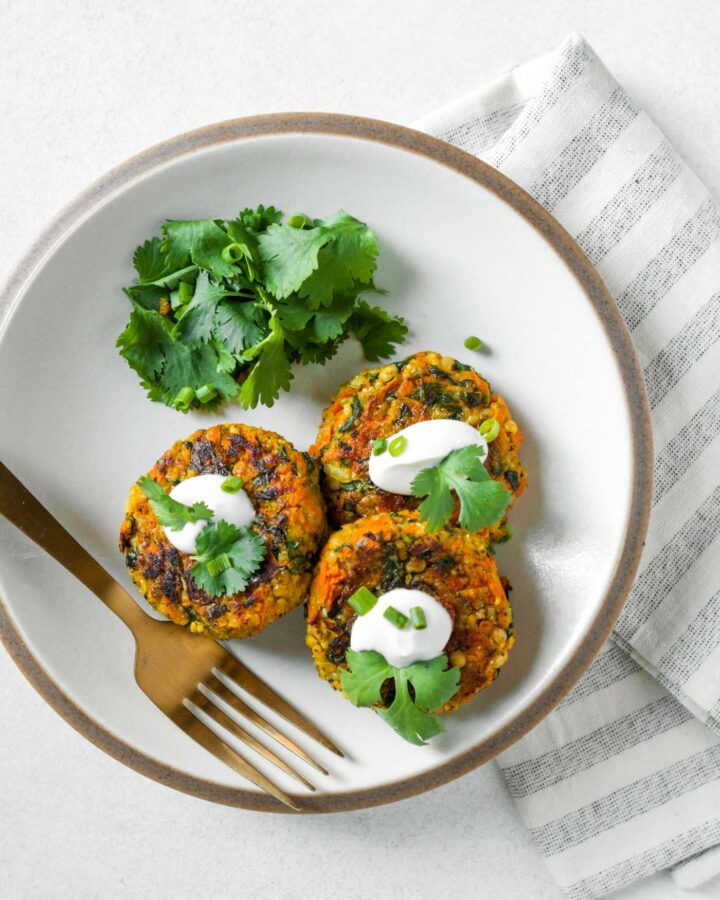 Sorghum can carrot veggie cakes set on a white plate