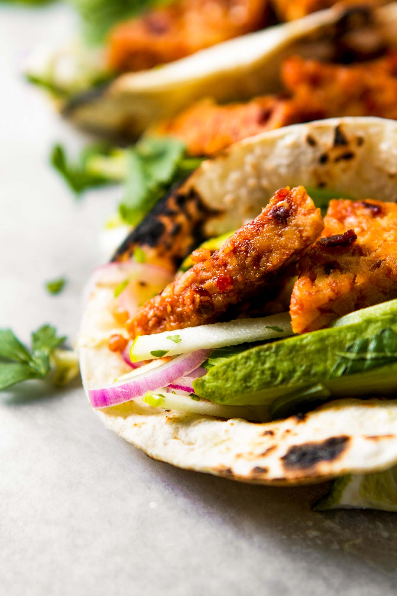 Close up photograph of marinated baked tempe stuffed into a tortilla with red onion, avocado, slaw and cilantro.