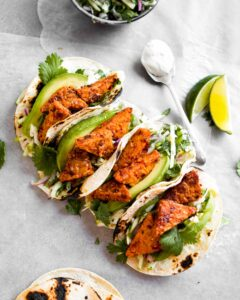 Overhead photo of vegan tempeh tacos arranged in a line across white paper with limes and a creamy sauce off to the side