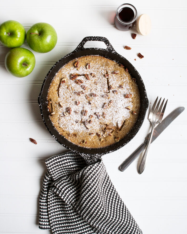 Photograph of a puffed apple pancake in a cast iron skillet on a white table