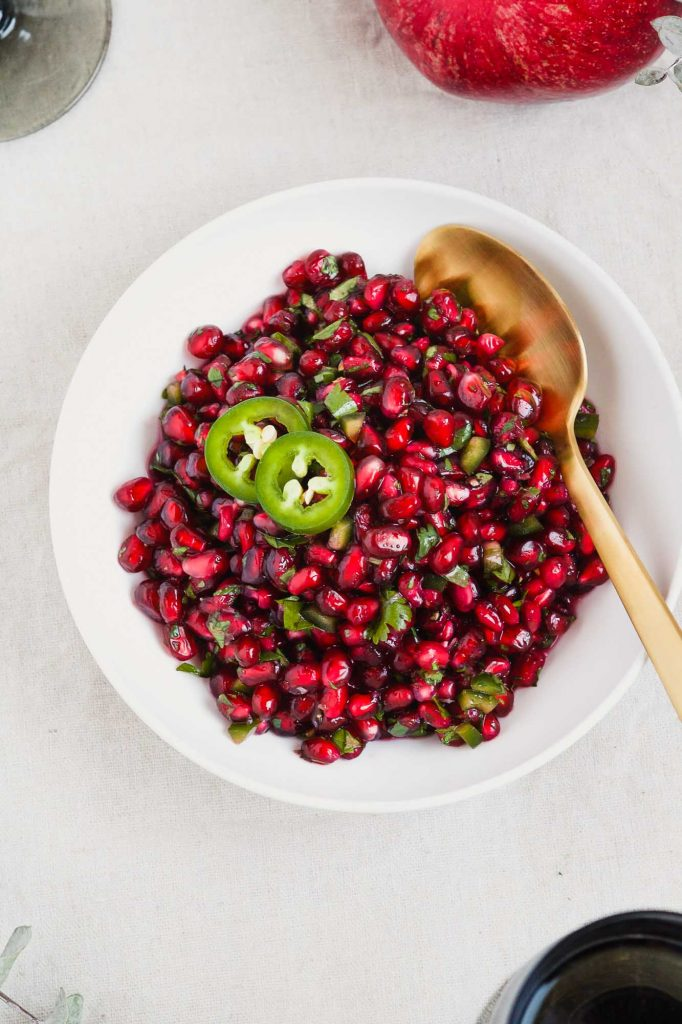 """overhead image of pomegranate relish or """"salsa"""" in a white bowl with greens set around it"""