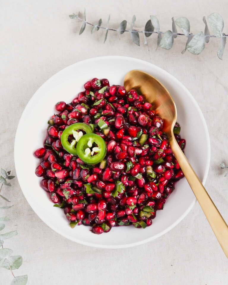 "overhead image of pomegranate relish or ""salsa"" in a white bowl with greens set around it"