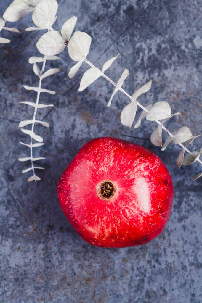 Overhead image of a fresh pomegranate on a blue counter