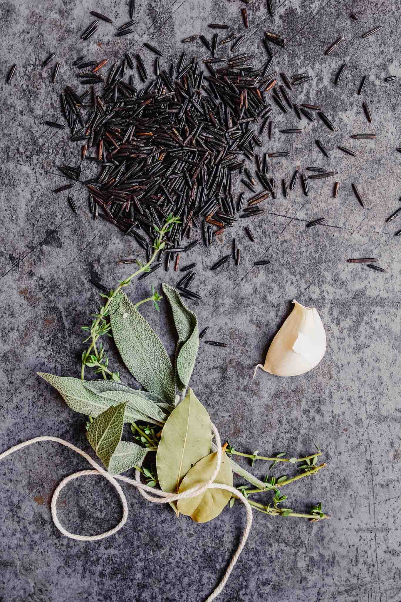 overhead image of wild rice and aromatics scattered over a blue countertop