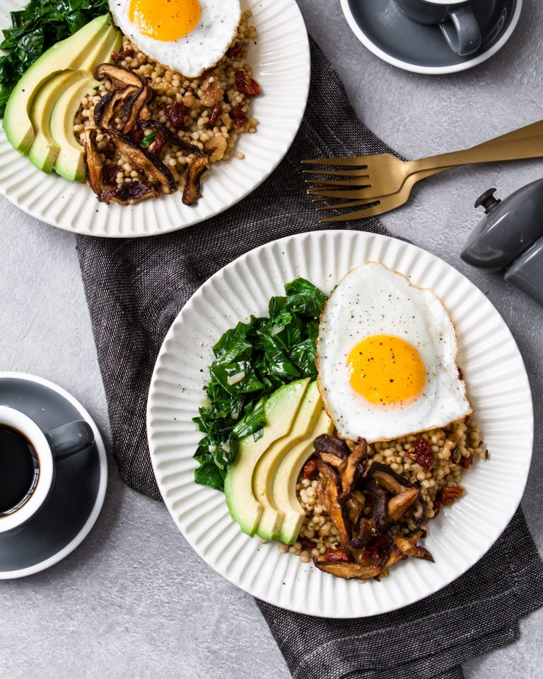 two white bowls with whole grains, sliced avocado, sautéed greens, topped with an egg