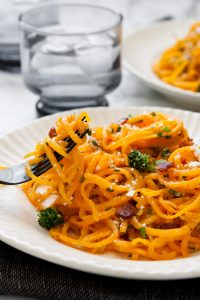Butternut squash noodles spun around a black fork with broccoli and bacon