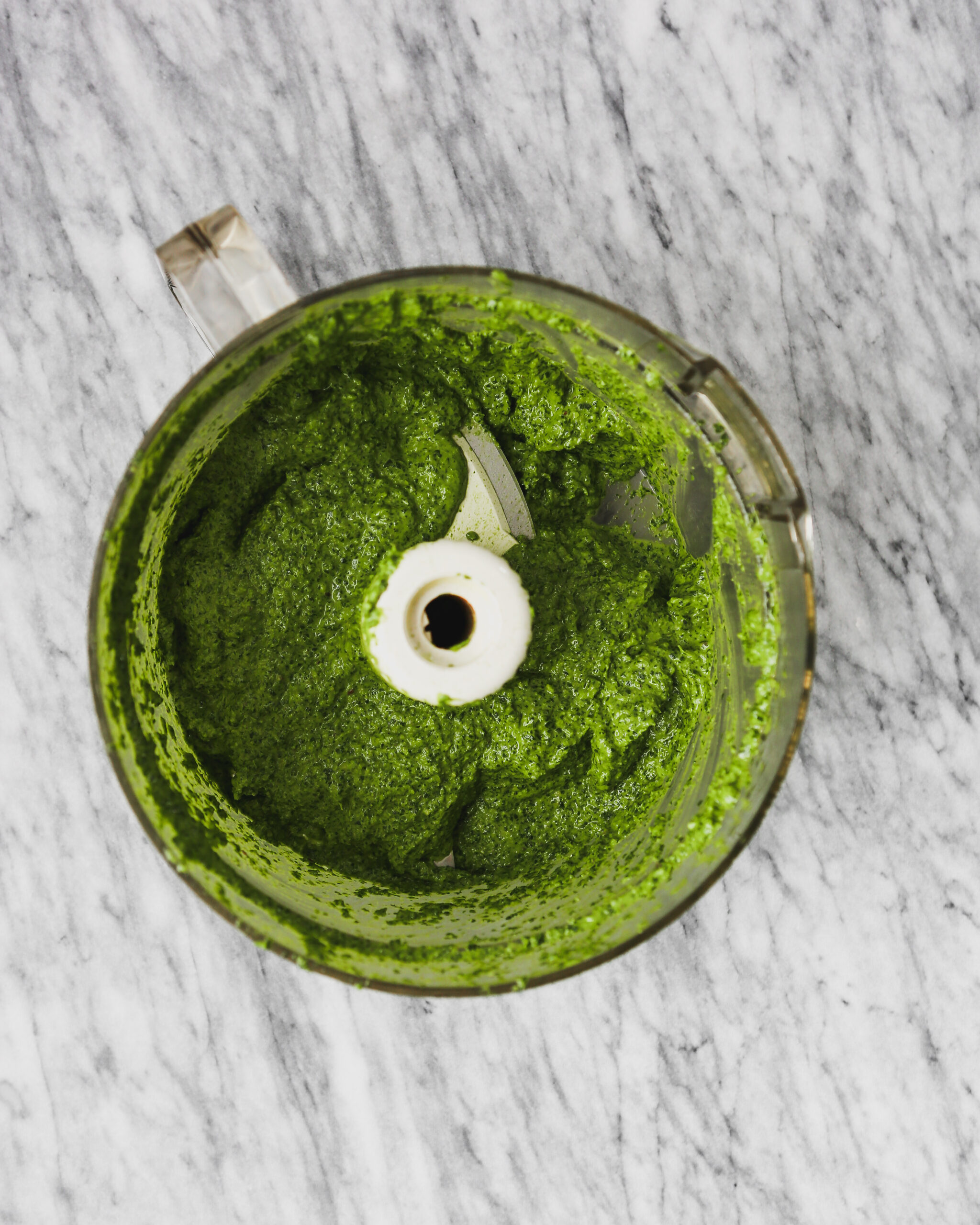 Pureed pesto in food processor on marble