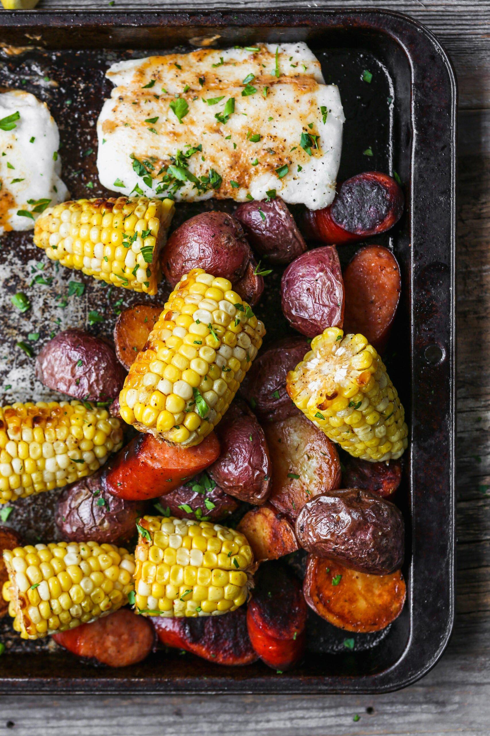 Roasted fish, potatoes, sausage, and corn on worn baking sheet.