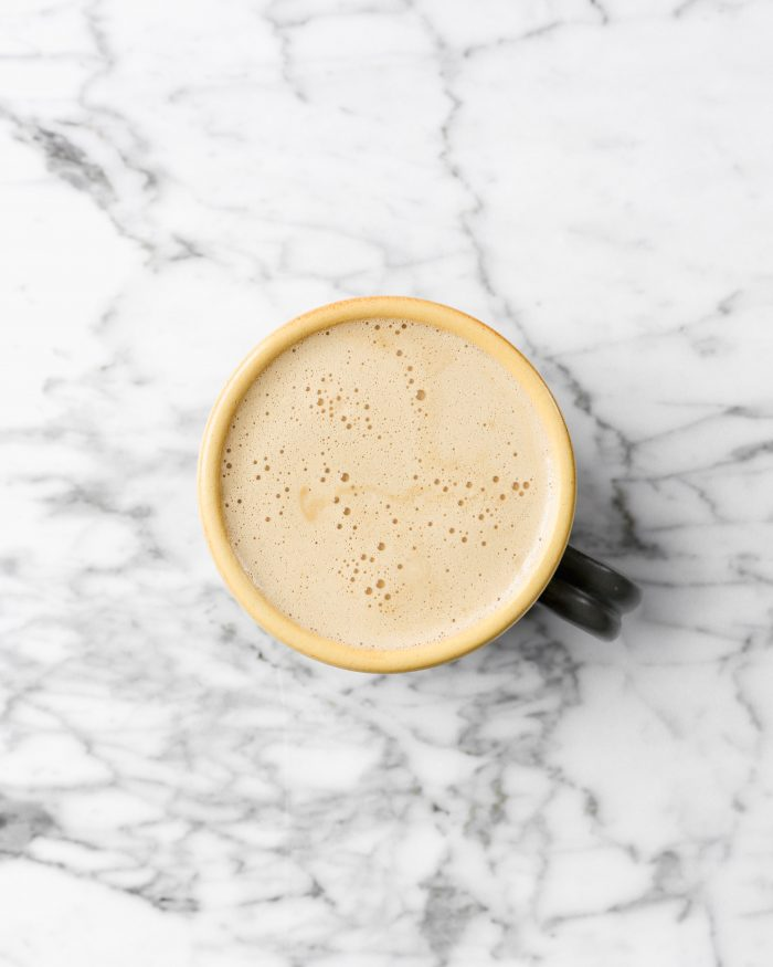 Latte in a mug set on a white marble background