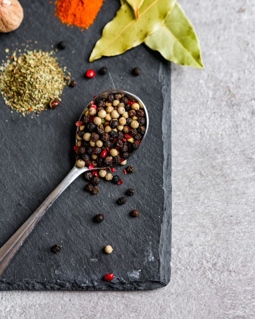 Multi-colored peppercorns spilling off of a spoon on black slate platter