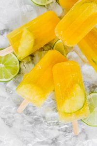 bright yellow popsicles set on a white marble surface