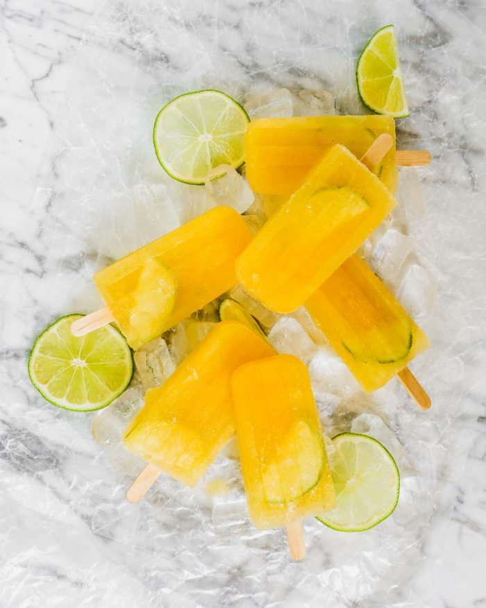 Bright yellow popsicles and lime slices set on a white marble surface
