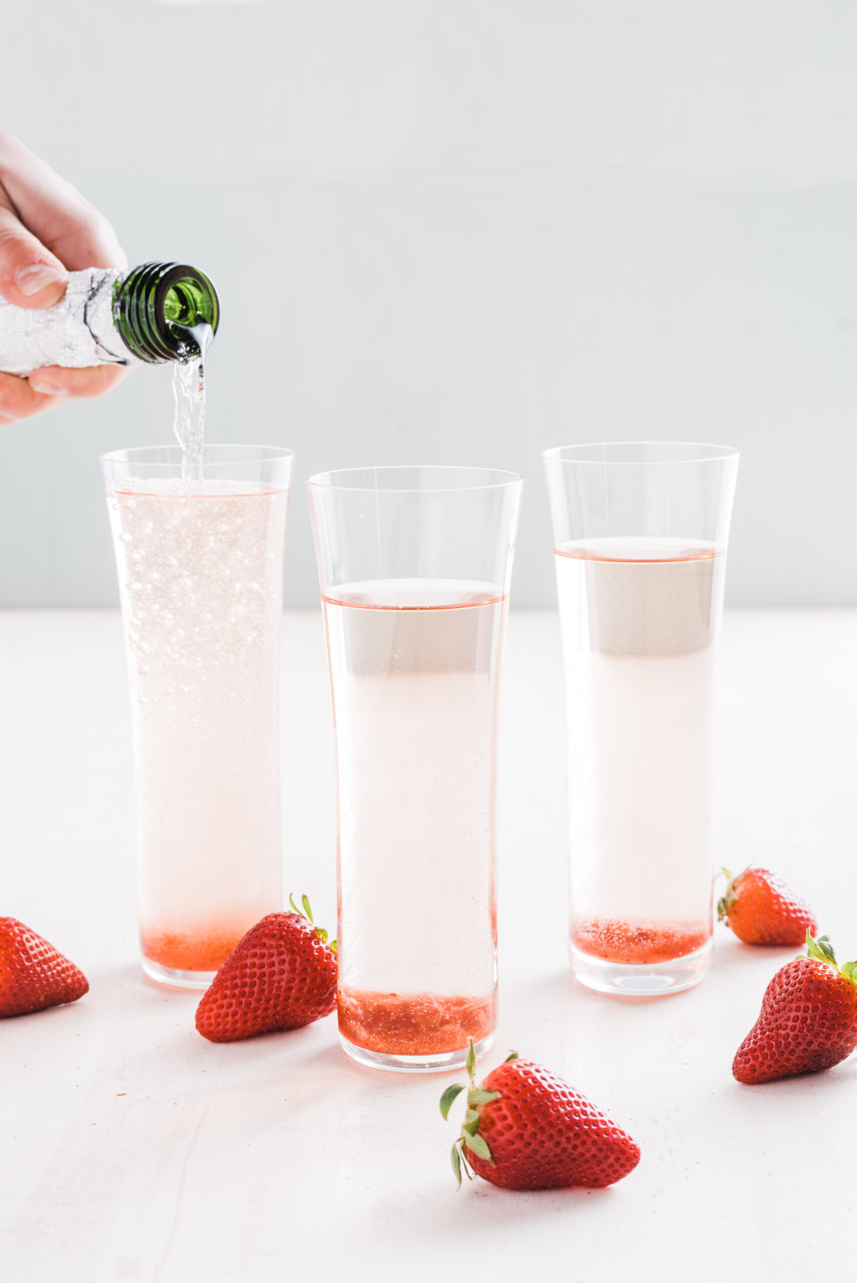 cocktail in tall flute glasses with strawberry slices on top.