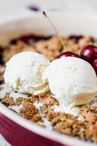 Cherry crisp in an oval baking dish set on a marble surface with servings of cherry crisp and scoops of ice cream in white bowls.