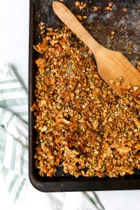 Homemade granola recipe on a black baking sheet with a white and green towel set to the side.